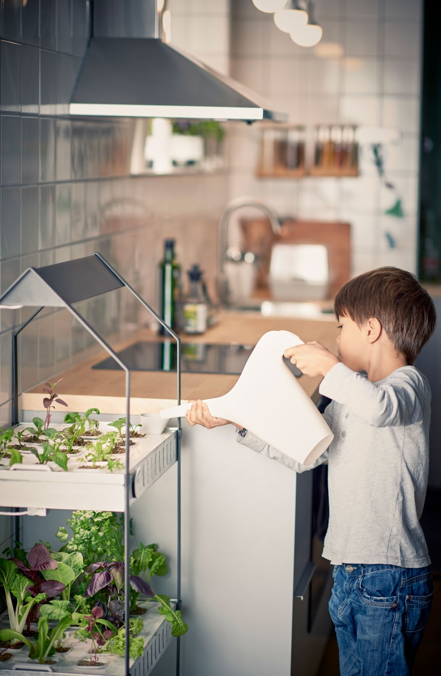 kid-watering-plants-in-the-ikea-vaxer-plant-stand