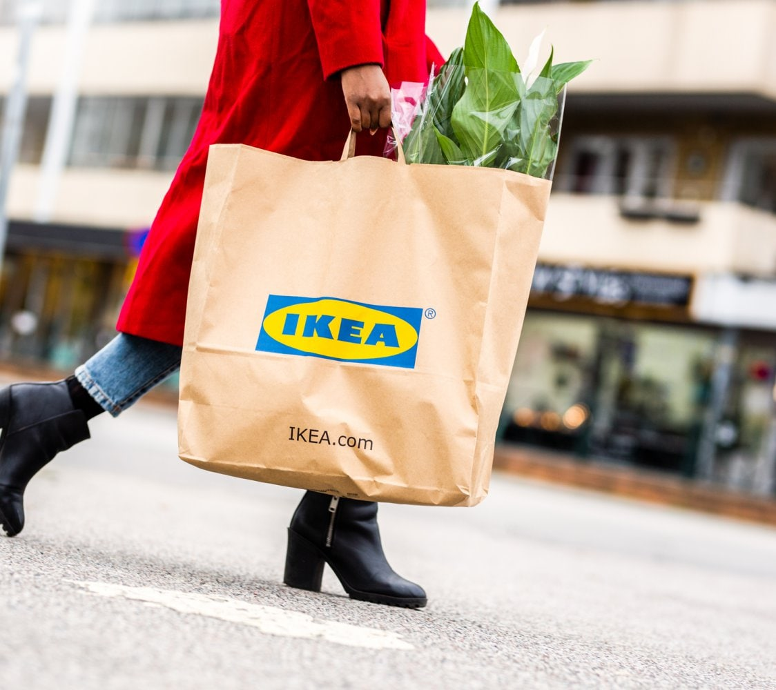 Woman walking in the streets with an IKEA bag with a peace lily.