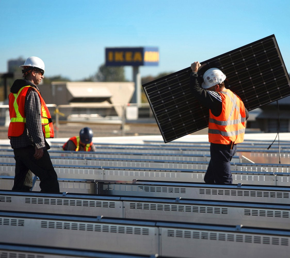 Construction workers installing solar panels at an IKEA store.
