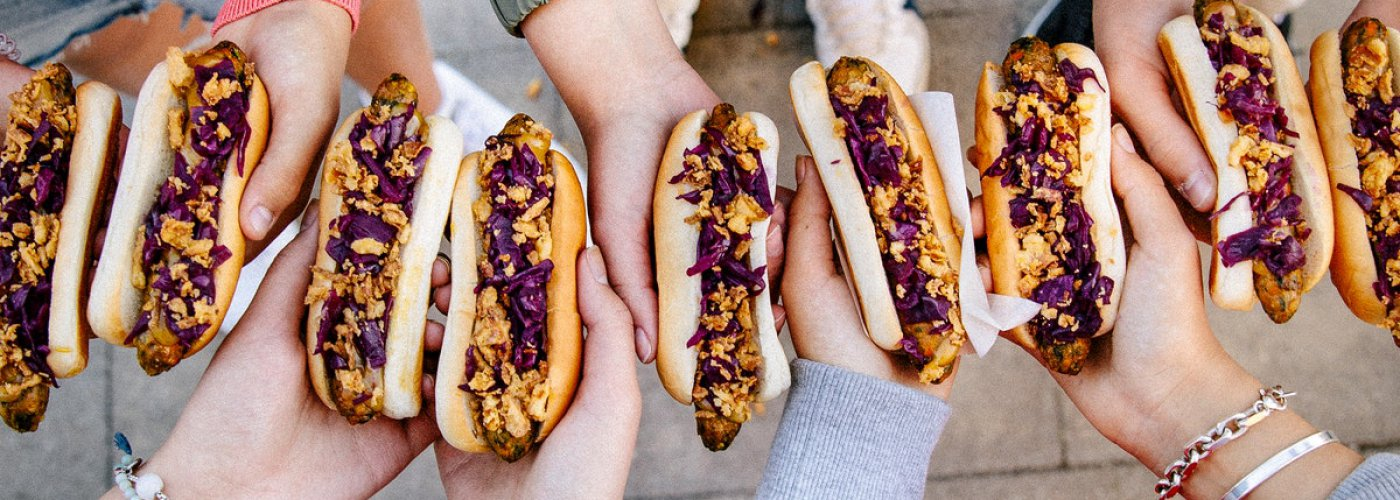A group of friends holding veggie hotdogs.