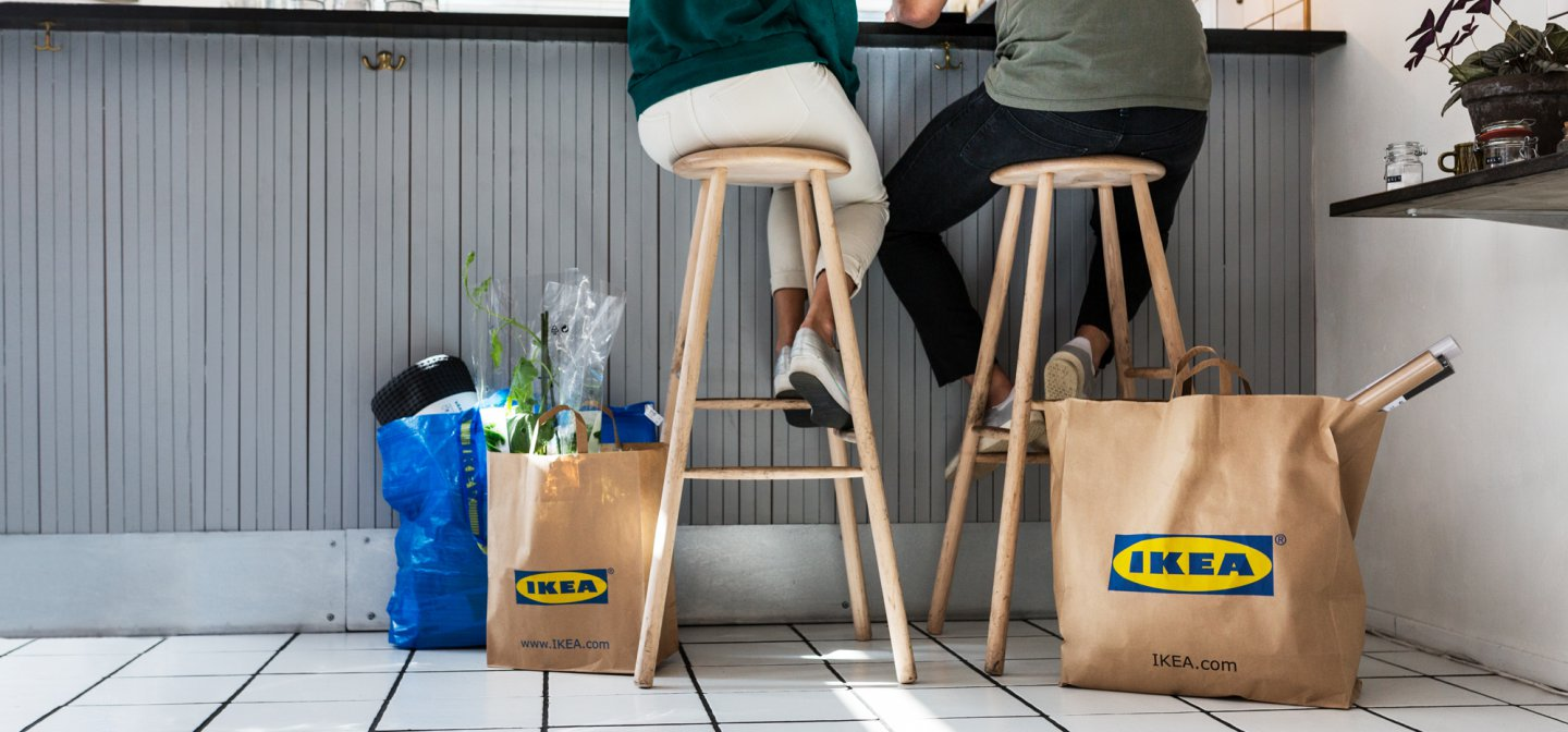 Friends sitting at a cafe with several bags from the IKEA store.