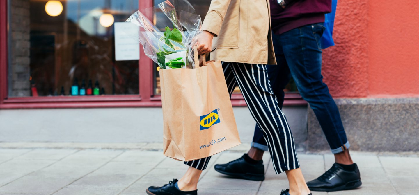 Two people walking, one holding an IKEA bag with a plant.