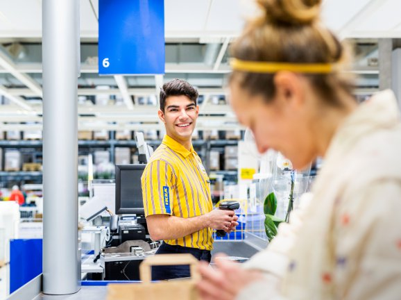 Cashier helping customer by the cash register in the IKEA store.