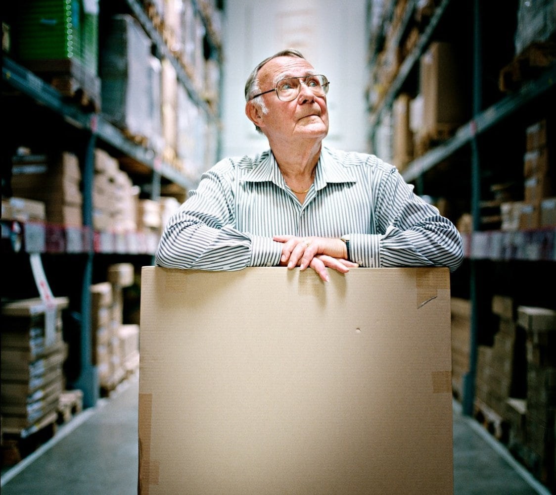Ingvar Kamprad standing in the IKEA store wear-house with a cardboard box.